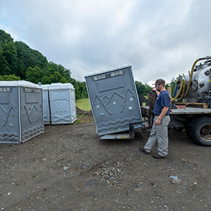 Septic worker moving portable toilet with truck